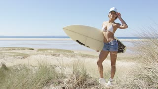 Attractive woman on the beach holding a surfboard and touching the cap in Tarifa, Cadiz, Spain.