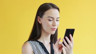 Attractive young female in striped clothing browsing modern smartphone while standing on bright yellow background