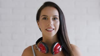 Attractive young lady with brown hair and modern headphones cheerfully smiling and looking at camera while standing on white background