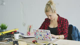 Attractive young woman in black top and checkered shirt sitting at wooden desk with tools and colorful laptop concentrating on writing in clipboard with white plastered wall on background .