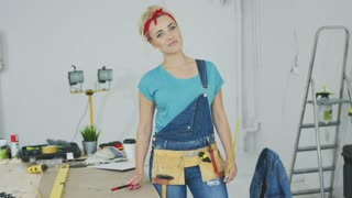 Attractive young woman in jeans overalls and tool belt standing relaxed at wooden desk with instruments in workshop looking at camera and smiling
