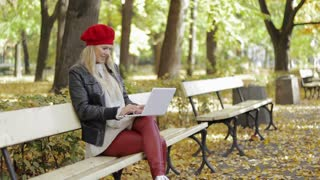 Attractive young woman in leather jacket and red beret sitting on bench and using laptop during walk in autumn park.