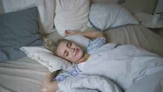 Attractive young woman in shirt lying on comfortable bed under soft blanket and stretching arms in morning.