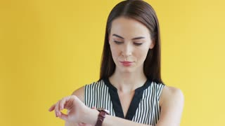Attractive young woman in striped clothing looking at stylish wristwatch while standing on bright yellow background