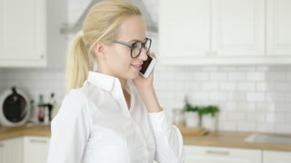 Attractive young woman in white shirt and glasses talking by smart phone while standing at modern kitchen.