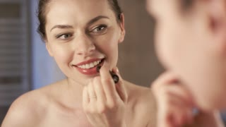 Attractive young woman looking at mirror and applying nice lipstick on delicate lips while standing in bathroom in morning.
