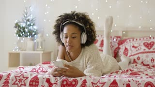 Attractive young woman relaxing at Christmas lying on her bed listening to music on her mobile with sparkling festive lights in the background