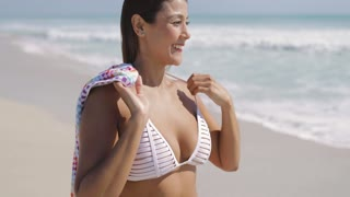 Attractive young woman standing on summer sandy beach and adjusting hair while holding the towel at the oceanside.