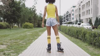 Back view of anonymous sportive girl in shorts and skates riding down sidewalk on background of street in summer.