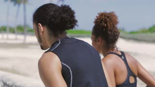 Back view of athletic ethnic handsome man and pretty woman jogging together in the park in sunny day.