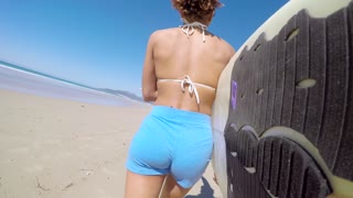 Back view of attractive young female surfer walking on the seashore with the camera attached to the surfboard and looking back. Horizontal outdoors shot.