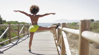 Back view of fit ethnic woman in bikini and sportive short warming up legs before workout on wooden pier with view of sea on background.