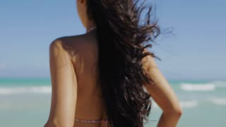 Back view of model with long black hair and fit body wearing pink bikini and walking on tropical ocean shoreline in bright sunshine.
