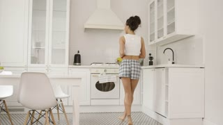Back view of young female wearing home clothing and dancing near counter in modern kitchen of white color.