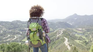 Back view of young happy woman with backpack standing with hands apart and enjoying mountains in summer.