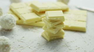 Bar of white chocolate with little pieces placed near one on another and round sweets covered with coconut flakes on white tablecloth