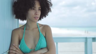 Beautiful African-American woman with short hairstyle holding hands crossed looking away on beach house.