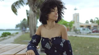 Beautiful black girl in stylish blouse holding hands behind head and enjoying fresh wind with eyes closed sitting on beach.
