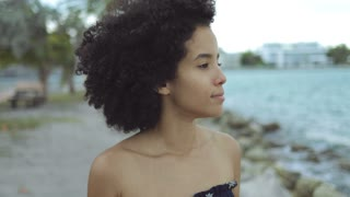 Beautiful black woman with waving curls holding hands apart while standing on coastline in wind and looking away.