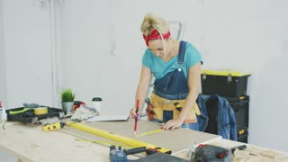 Beautiful blond female in jeans overalls and carpenter belt drawing line with pencil and ruler on plywood sheet placed on workbench with tools