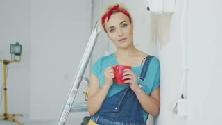 Beautiful blond woman in jeans overalls and red headband standing relaxed with mug of hot drink leaning on shoulder against white unpainted wall and looking at camera smiling.