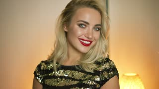 Beautiful blonde woman in perfect evening outfit charmingly smiling and looking at camera while standing in brightly lit room.