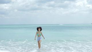 Beautiful confident African-American model in bikini and denim shorts walking on tropical ocean shoreline looking at camera.