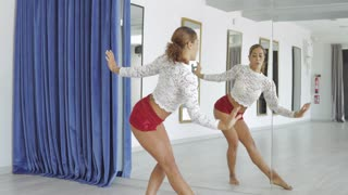 Beautiful confident dancer in shorts performing sensual dance standing in seductive pose and looking at mirror in spacious studio.