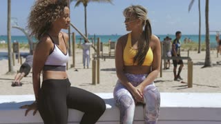Beautiful diverse women in sportive outfits sitting on tropical coastline with gym and chatting happily.