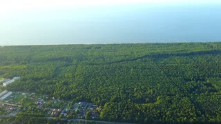 Beautiful drone shot from air of green spacious forest area and suburbs on background of blue sea water and horizon in sunlight.