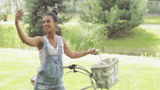 Beautiful ethnic woman in denim overall smiling happily while posing for selfie in summer park and standing with bicycle.