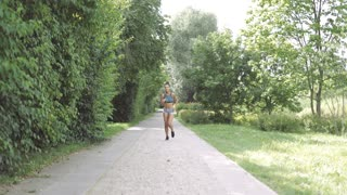 Beautiful ethnic woman in shape wearing sportive clothing listening to music and jogging on road in summer green park.