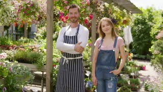 Beautiful girl in denim overall and handsome man in apron standing in wonderful garden with green plants working together.