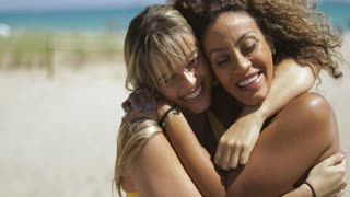 Beautiful laughing multiracial women embracing strongly in happiness while sitting on coastline of ocean.
