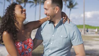 Beautiful multiracial couple in summer clothes embracing and having fun on waterfront in bright sunlight looking at each other.