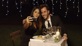 Beautiful romantic couple enjoying an elegant dinner in a restaurant posing for a selfie smiling into the camera on their mobile phone