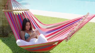 Beautiful single young woman in white pants and bikini top laying down in hammock while using phone