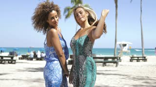 Beautiful vivacious multiethnic women in trendy overalls embracing in happiness and looking at camera in sunlight on beach.
