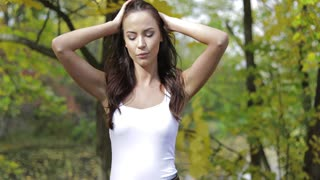 Beautiful woman in white tank top walking in autumn park on sunny day and smoothing her hair.