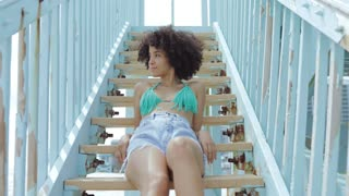 Beautiful young African-American girl in bikini and denim sitting on stairs of beach house looking at camera.