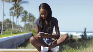 Beautiful young black woman sitting and using smartphone on fence in sunny summer day on the background of the sea.