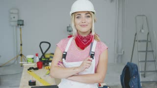 Beautiful young blond woman in white safety helmet and overalls with red bandana around neck looking at camera and smiling standing with pencil at workplace with desk, tools and stepladder