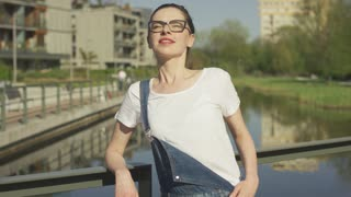 Beautiful young female in eyeglasses leaning her back on handrail above water in city and looking at camera.