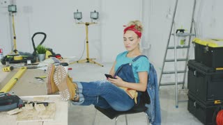 Beautiful young female in jeans overalls and red headband sitting relaxed with legs on desk with tools and using mobile phone in hand