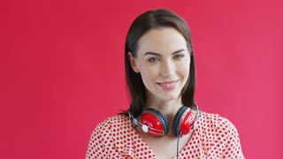 Beautiful young lady with modern headphones smiling and looking at camera while standing on red background