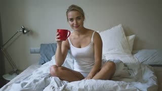 Beautiful young woman holding mug with hot beverage and looking at camera while sitting on comfortable bed.