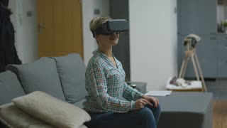 Beautiful young woman in checkered shirt sitting on sofa and wearing VR headset with astonished face expression.