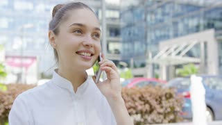 Beautiful young woman in formal clothing talking smartphone while smiling away on background of street in sunny day.