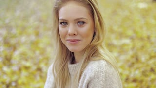 Beautiful young woman in soft beige jumper spending her time in autumn park on sunny day.