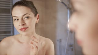 Beautiful young woman looking at mirror and touching skin on soft skin while applying cream in morning.